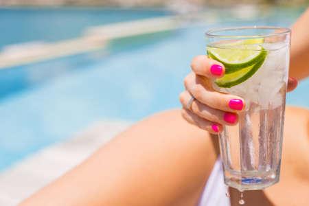 frio: Mujer que sostiene la bebida fría refrescante mientras toma el sol en la piscina