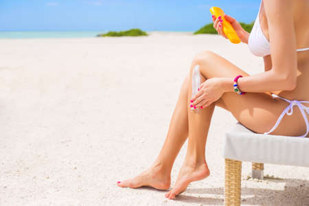 creme: Woman using sunscreen on the beach