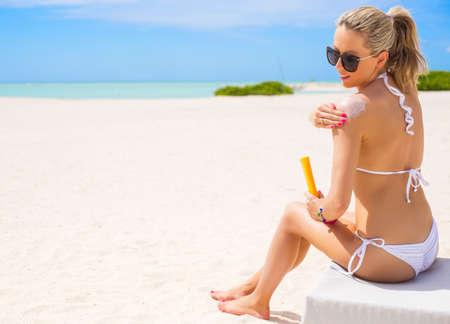 sonnenbaden: Frau Sonnenbaden am Strand und Anwendung von Sonnenschutzcreme