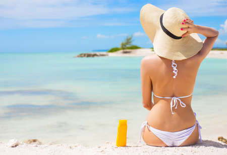 skin care products: Woman sunbathing on the beach Stock Photo