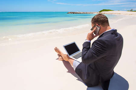 Businessman working with computer and talking on phone on the beach photo