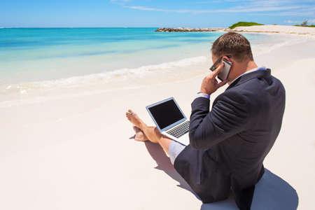 Zakenman werken met de computer en praten over de telefoon op het strand Stockfoto
