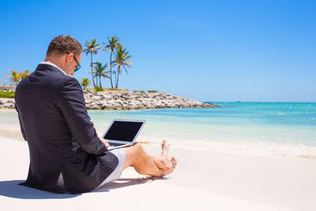열 대 해변에서 랩톱 컴퓨터를 사용하는 사업가