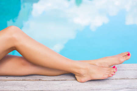 human toe: Beautiful women legs by the swimming pool