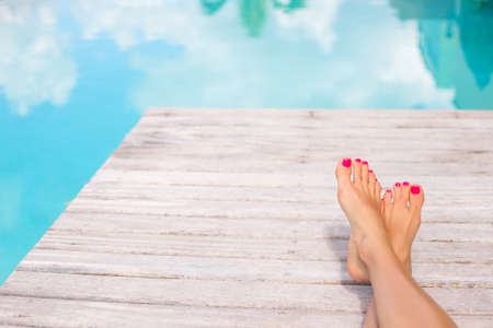 bare women: Bare woman feet on wooden deck by the swimming pool