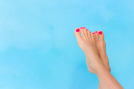 Bare woman feet over blue swimming pool water Stockfoto