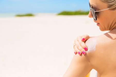jolie fille: Femme appliquer un �cran solaire � la plage sur la chaude journ�e d'�t�