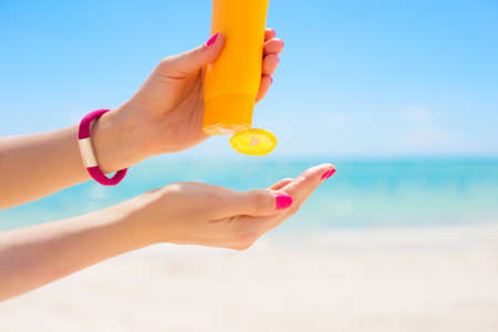 Woman using sunscreen Stock Photo