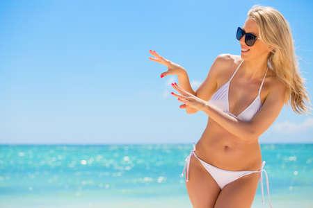 Vrolijke vrouw in witte bikini op het strand Stockfoto