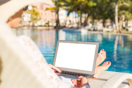 usando computadora: Mujer que usa el ordenador portátil en la piscina Foto de archivo
