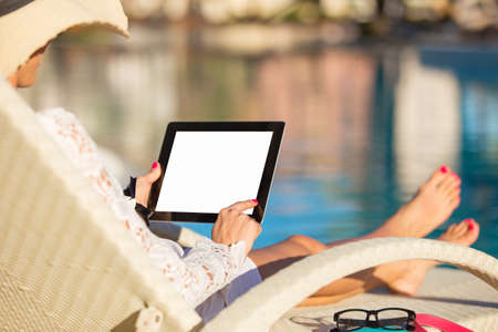 Woman using tablet computer by the pool photo
