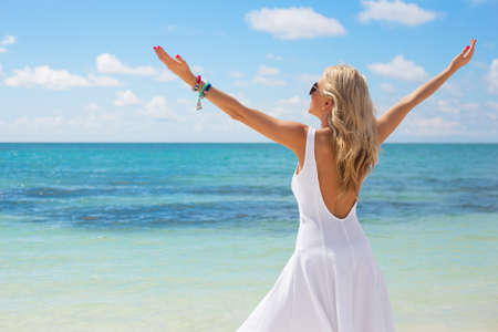 stress free: Young woman in white dress enjoying summer day on the beach Stock Photo