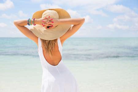 phụ nữ trẻ trong trang phục màu trắng và chiếc mũ rơm trên bãi biển