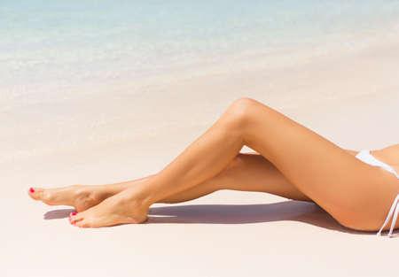 petite fille maillot de bain: Les jambes de Belle mince femme sur la plage Banque d'images