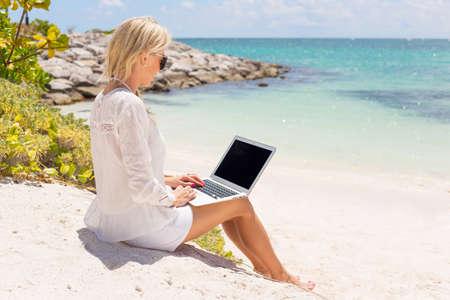 obreros: Empresaria que trabaja con el ordenador en la playa Foto de archivo