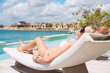 pool deck: Woman relaxing in deck chair by the pool Stock Photo
