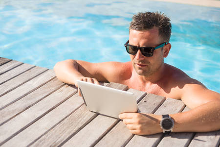 man working on computer: Man using tablet computer while relaxing in the pool