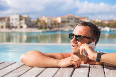calling on phone: Man talking on phone while relaxing in the swimming pool