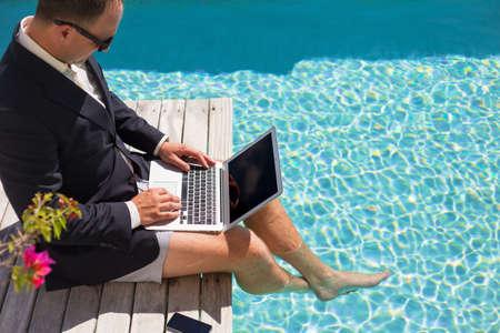 プールサイドのラップトップ コンピューターで作業するビジネスマン