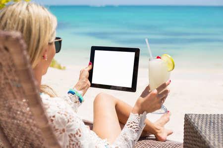 convés: Mulher relaxada usando o computador tablet na praia