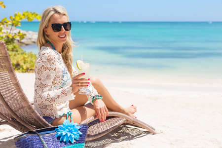 sillon: Mujer beber un c�ctel y relajarse en la silla en la playa Foto de archivo