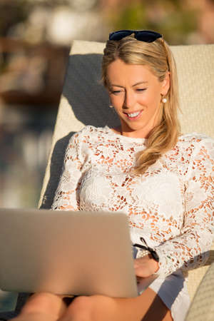Vertical photo of woman using laptop computer while sitting in deck chair photo