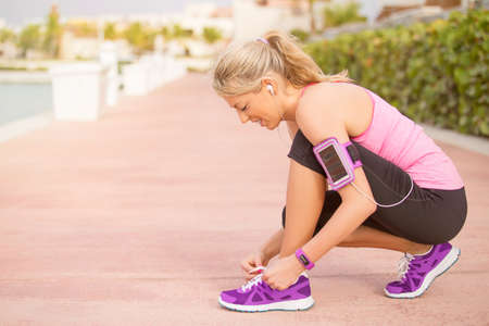 energized: Active sporty girl tying shoes before morning workout Stock Photo