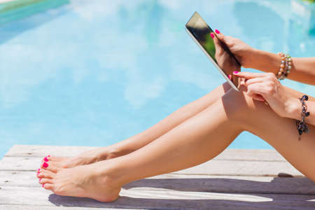 Woman holding digital tablet outdoors by the swimming pool photo
