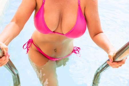 Curvy woman in pink bikini getting out of swimming pool