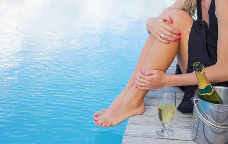 Zitting van de dame bij het zwembad focus op champagneglas