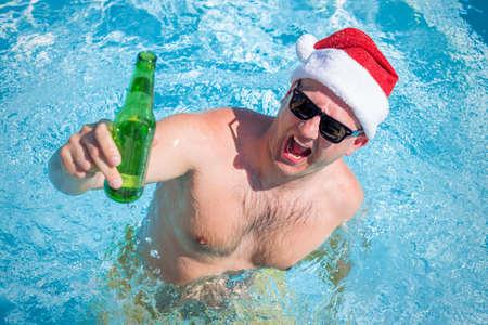 borracho: Hombre con sombrero de santa fiesta en la piscina con la botella de cerveza en la mano