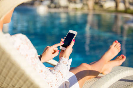 lady with phone: Woman sitting in deck chair and using mobile phone