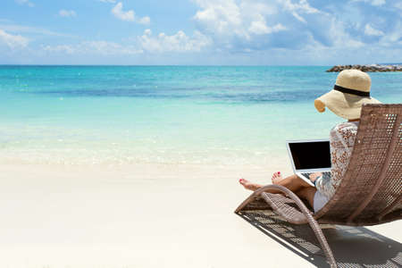 vacaciones en la playa: Mujer de negocios usando la computadora portátil en la playa