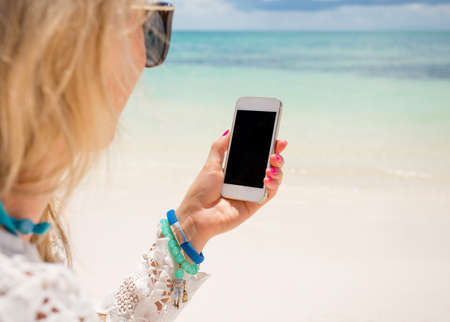 woman on phone: Woman holding smartphone in hand on the beach