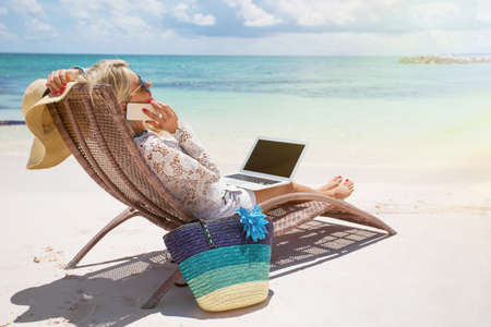 woman at work: Productive businesswoman working on the beach
