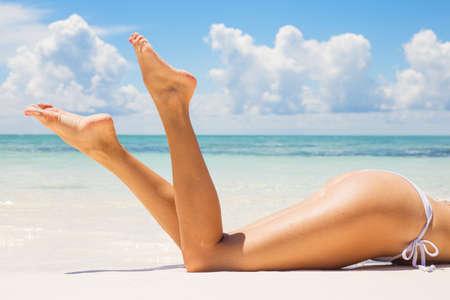 Красиво загорелые ноги на пляже