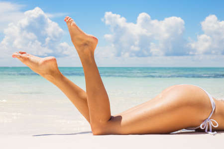tan woman: Beautifully tanned legs on the beach