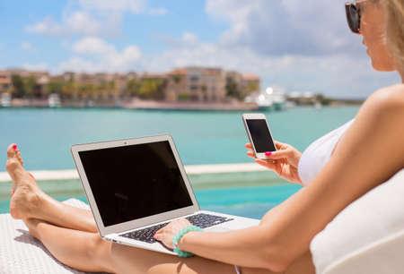 Drukke zakelijke vrouw met behulp van computer en mobiele telefoon bij het zwembad