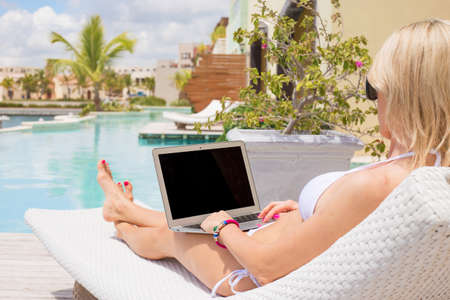 Woman sitting in deck chair and using laptop computer