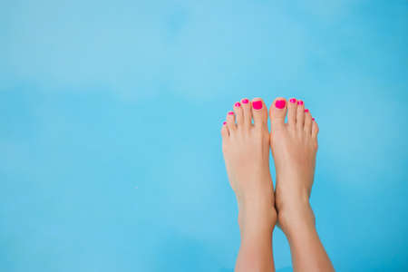female feet: Bare feet over blue swimming pool water Stock Photo