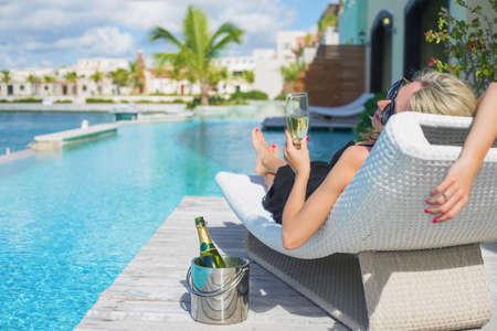 tomando alcohol: Señora que se relaja en silla de cubierta en la piscina y bebiendo champán Editorial