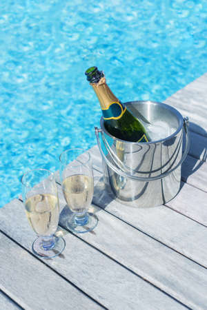 Vertical photo of champagne bottle in bucket and two glasses of champagne on the deck by the swimming pool