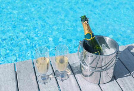 brindisi spumante: Freddo bottiglia di champagne in un secchio di ghiaccio e due bicchieri di champagne sul ponte a bordo piscina