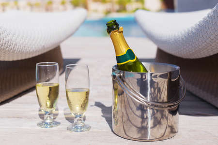 pool party: Champagne bottle in bucket and two glasses of champagne