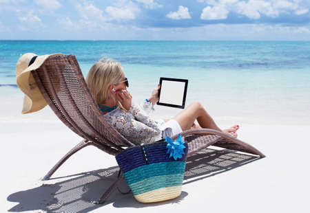 Vrouw ontspannen op het strand en het luisteren naar muziek op haar digitale tablet computer