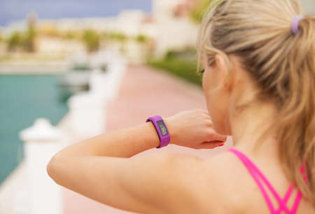 cardio workout: Woman looking at her smartwatch during workout Stock Photo