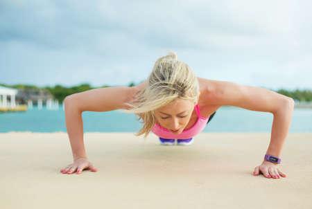 pushups: Woman doing pushups exercise Stock Photo