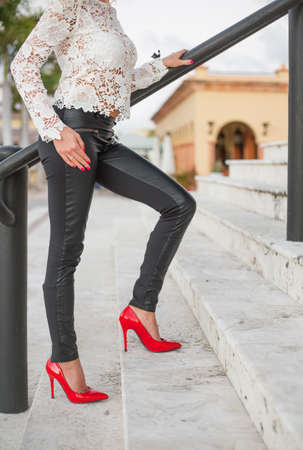 Lady in red high heel shoes standing on stairs