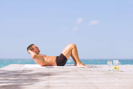 situps: Young fit man doing abs crunches exercise outdoors
