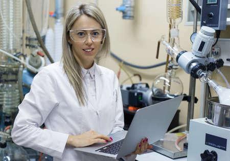 química: Mujer con el ordenador portátil de trabajo en el laboratorio de química